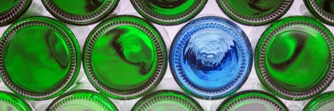 Frasco azul de vidro entre frascos verdes Foto de Stock Royalty Free