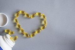 Frasco branco com as cápsulas amarelas dispersadas das vitaminas em uma tela cinzenta Imagem de Stock Royalty Free