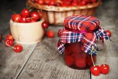 Frasco com as cerejas na tabela de madeira Fotografia de Stock