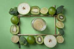Frasco com limonada em um quadro de frutos verdes imagem de stock royalty free