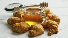 Frasco com mel e croissant filme