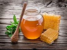 Frasco completamente do mel e dos favos de mel frescos Fotos de Stock Royalty Free
