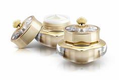 Frasco cosmético da coroa dois dourada no branco Imagens de Stock Royalty Free