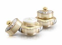 Frasco cosmético da coroa dois dourada no branco Foto de Stock Royalty Free