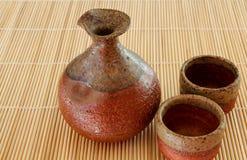 Frasco da causa e dois copos em uma esteira de bambu Fotos de Stock Royalty Free