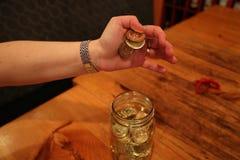 Frasco da mão da mulher completamente das moedas Fotografia de Stock