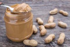 Frasco da manteiga de amendoim com porcas Na textura de madeira Imagem de Stock Royalty Free