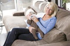 Frasco de alimentação da mamã ao bebê em casa no sofá Imagem de Stock