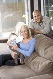 Frasco de alimentação dos pais ao bebê em casa no sofá Fotografia de Stock Royalty Free