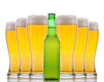 Frasco de cerveja na frente dos vidros cheios fotografia de stock royalty free