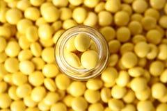 Frasco de cristal con las tablillas amarillas redondas Foto de archivo libre de regalías