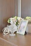 Frasco de cristal da joia com moldura para retrato e flores na tabela de madeira Fotografia de Stock