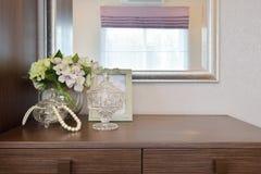 Frasco de cristal de Jewery com moldura para retrato e flores na tabela de madeira Fotos de Stock