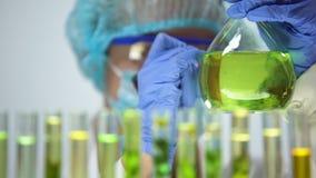 Frasco de la marca del investigador con el líquido verde, experimento químico acertado, laboratorio almacen de metraje de vídeo