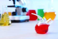 Frasco de la réplica con la muestra en la tabla en laboratorio de química fotos de archivo