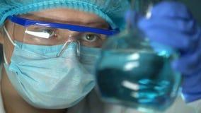 Frasco de la tenencia del experto del laboratorio con el líquido transparente azul, comprobando calidad metrajes