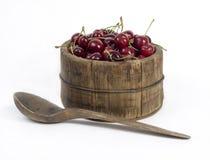 Frasco de madeira completamente de cerejas vermelhas Imagens de Stock