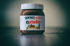 Frasco de Nutella sobre uma tabela de madeira fotos de stock royalty free