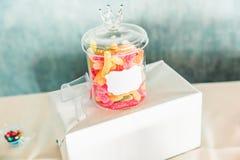 Frasco de vidro colorido dos doces na tabela doce da barra fotografia de stock royalty free