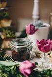 Frasco de vidro com azeitonas ao lado das tulipas cor-de-rosa imagens de stock