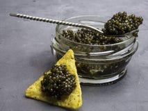 Frasco de vidro com caviar preto, e colher de prata, microplaquetas Alimento saud?vel Copie o espa?o fotografia de stock