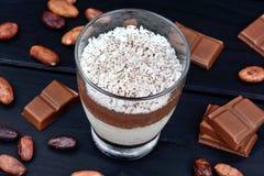 Frasco de vidro com musse de flocos do chocolate e do coco no fundo de madeira fotos de stock