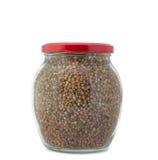 Frasco de vidro com o tampão vermelho fechado do trigo mourisco isolado Imagens de Stock