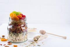 Frasco de vidro com os ingredientes para cozinhar o granola no fundo branco Flocos, mel, porcas, frutos secos e sementes da aveia Fotografia de Stock Royalty Free