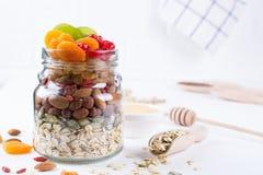 Frasco de vidro com os ingredientes para cozinhar o granola no fundo branco Flocos, mel, porcas, frutos secos e sementes da aveia imagem de stock royalty free
