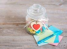 Frasco de vidro com tampa e deslizamentos de papel coloridos para dentro Imagem de Stock Royalty Free