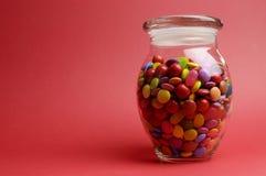 Frasco de vidro completamente de lollies e de doces coloridos brilhantes com a tampa fechado com espaço da cópia. Fotos de Stock Royalty Free