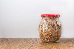 Frasco de vidro completo com o tampão vermelho fechado do trigo mourisco sobre Imagem de Stock