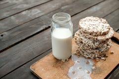 Frasco de vidro do leite caseiro, pão estaladiço delicioso na tabela de madeira do fundo Fotografia de Stock Royalty Free