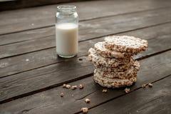Frasco de vidro do leite caseiro, pão estaladiço delicioso na tabela de madeira do fundo Imagens de Stock Royalty Free