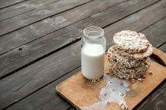 Frasco de vidro do leite caseiro, pão estaladiço delicioso na tabela de madeira do fundo Foto de Stock Royalty Free