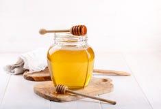 Frasco de vidro do mel e do dipper de madeira no branco fotos de stock