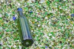 Frasco de vinho em uma cama do vidro despedaçado Fotografia de Stock