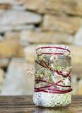 Frasco decorado com rosas e laço em um fundo de pedra Decoração Home Foto de Stock