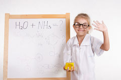 Frasco del químico de la muchacha en un tablero con la inscripción Imagen de archivo