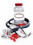 Frasco do comprimido, comprimidos vermelhos e um estetoscópio Fotografia de Stock Royalty Free
