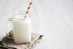 Frasco do leite frio com guardanapo em um fundo de madeira branco, vista lateral fotografia de stock