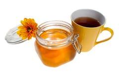 Frasco do mel e copo de chá, isolado Imagens de Stock