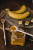 Frasco do mel e das bananas na tabela de madeira Imagem de Stock Royalty Free