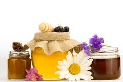Frasco do mel fresco com drizzler e das flores isoladas no fundo branco Imagem de Stock Royalty Free
