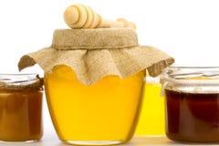 Frasco do mel fresco com drizzler e das flores isoladas no fundo branco Foto de Stock Royalty Free