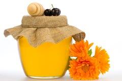 Frasco do mel fresco com drizzler e das flores isoladas no fundo branco Fotos de Stock