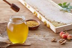 Frasco do mel, pólen da abelha e favos de mel na tabela de madeira Fotografia de Stock Royalty Free