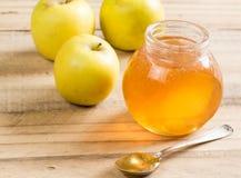 Frasco e colher da geleia de Apple com as maçãs do smith de avó na aba de madeira fotografia de stock royalty free