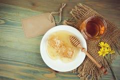 Frasco e favos de mel do mel sobre o fundo rústico de madeira Fotografia de Stock
