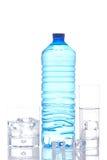 Frasco e vidros da água mineral com cubos de gelo Foto de Stock